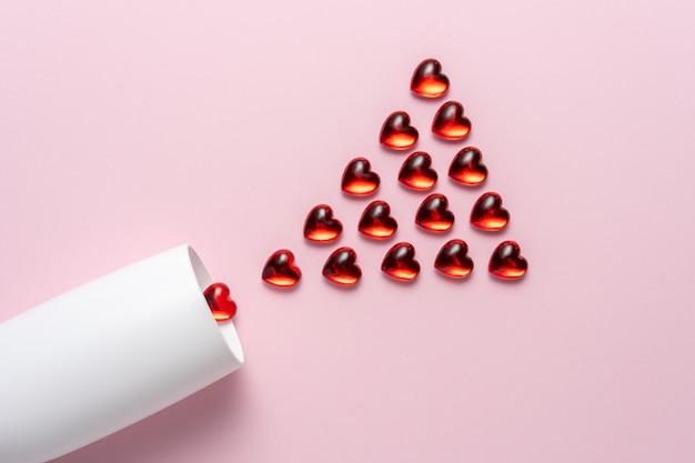Białe kieliszki do szampana z czerwonymi szklanymi sercami na różowej powierzchni.