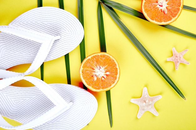 Białe klapki, owoce pomarańczy, rozgwiazdy i palmy