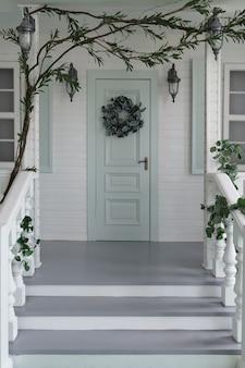 Białe klasyczne drewniane wejście do domu i schody