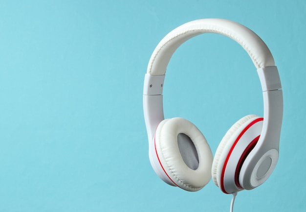 Białe klasyczne słuchawki przewodowe na białym tle na niebieskim tle. styl retro. minimalistyczna koncepcja muzyki.