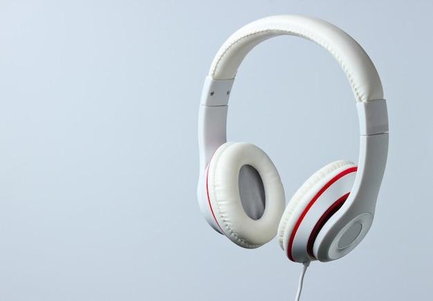 Białe klasyczne słuchawki przewodowe na białym tle na szarym tle. styl retro. minimalistyczna koncepcja muzyki.