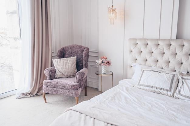 Białe klasyczne wnętrze sypialni z świątecznym bukietem w wazonie