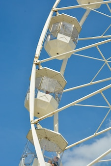 Białe koło promowe wesołego miasteczka na niebieskim niebie
