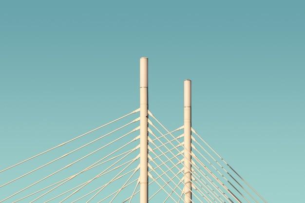 Białe kolumny i kable mostu z niebieskim niebem w tle