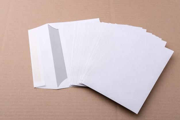 Białe koperty pocztowe są porozrzucane na stole