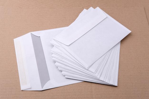 Białe koperty pocztowe są równomiernie rozmieszczone na stole