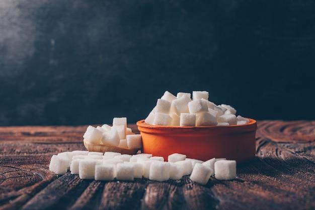 Białe kostki cukru w pomarańczowej misce z bocznym widokiem łyżki na ciemnym i drewnianym stole
