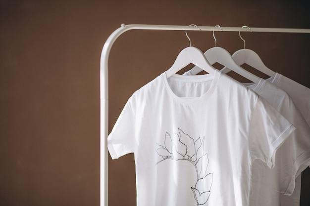 Białe koszule wiszące w pokoju