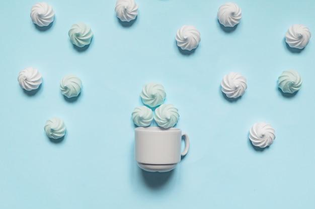 Białe kręcone bezy w porcelanowym pucharze na błękitnym tle, kartka z pozdrowieniami, kopii przestrzeń