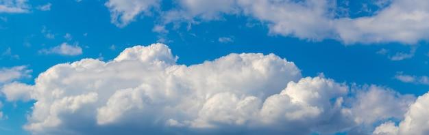 Białe kręcone chmury na niebieskim niebie, panorama nieba