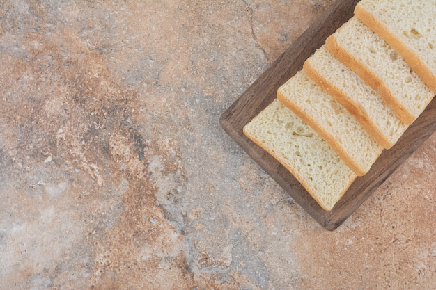 Białe kromki tosty na drewnianej desce