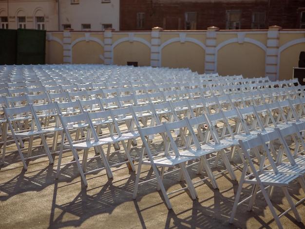 Białe krzesła dla widzów koncertowych na ulicy