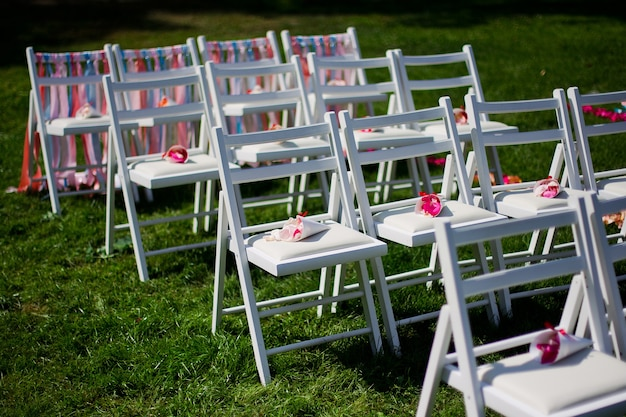 Białe krzesła do ceremonii ślubnej na zielonej łące w kolorowe paski