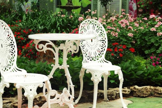 Białe krzesła i okrągły stół w ogrodzie kwiaty.