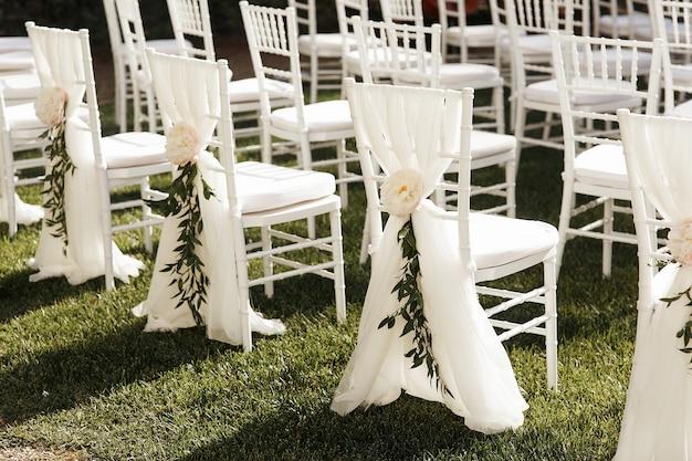 Białe krzesła ozdobione peonami i zielenią stoją na zewnątrz
