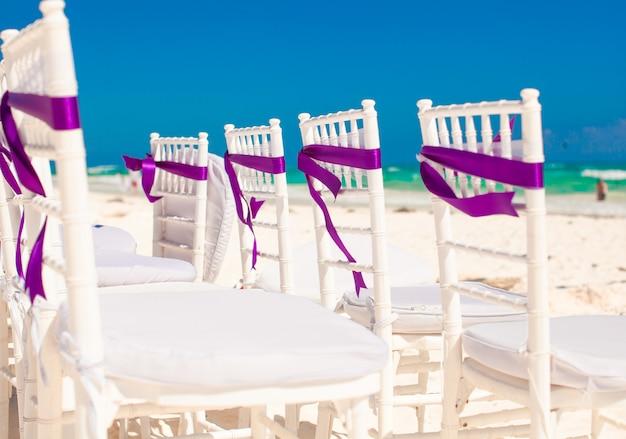 Białe krzesła ślubne ozdobione fioletowymi kokardkami na piaszczystej plaży