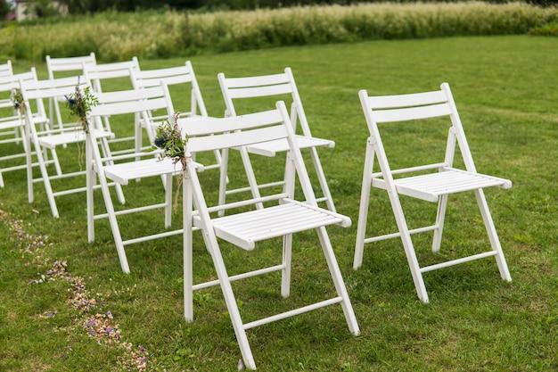 Białe krzesła weselne ozdobione świeżymi kwiatami na zielonej trawie. puste drewniane krzesła dla gości na zielonym trawniku w ogrodzie przygotowane na ślub.