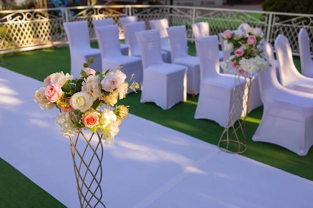 Białe krzesła z różowymi kokardkami do rejestracji wyjścia weselnego.
