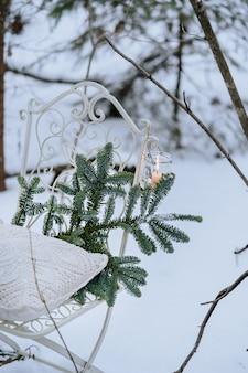 Białe krzesło ozdobione zapaloną świecą i świerkową gałęzią w lesie