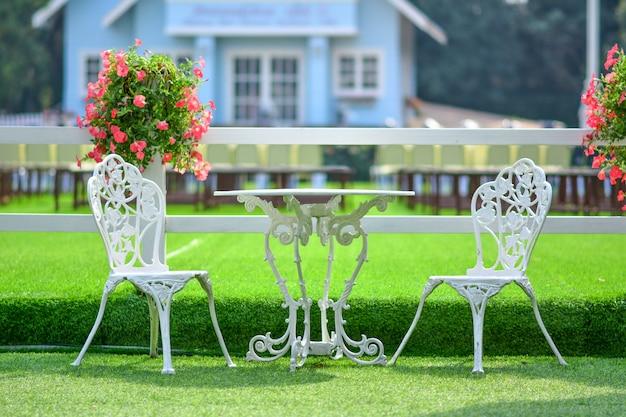 Białe krzesło w ogrodzie kwiatowym.