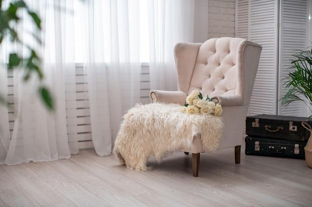 Białe krzesło w stylu angielskim na białej ścianie i duże okno z zasłoną.