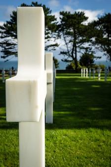 Białe krzyże na amerykańskim cmentarzu wojennym w pobliżu plaży omaha, normandia (colleville-sur-mer), fr
