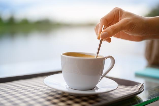 Białe kubki do kawy ułożone na zewnątrz w kawiarni.