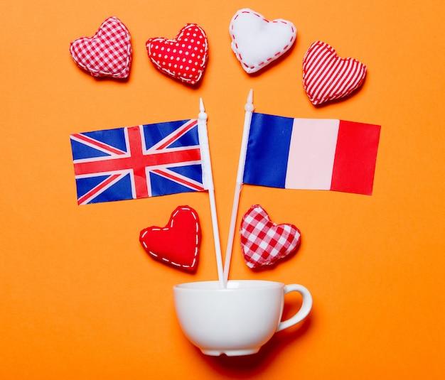 Białe kubki i kształty serca z flagami francji i wielkiej brytanii