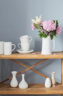 Białe kubki i kwiaty na wazonie na drewnianej półce na szarym tle