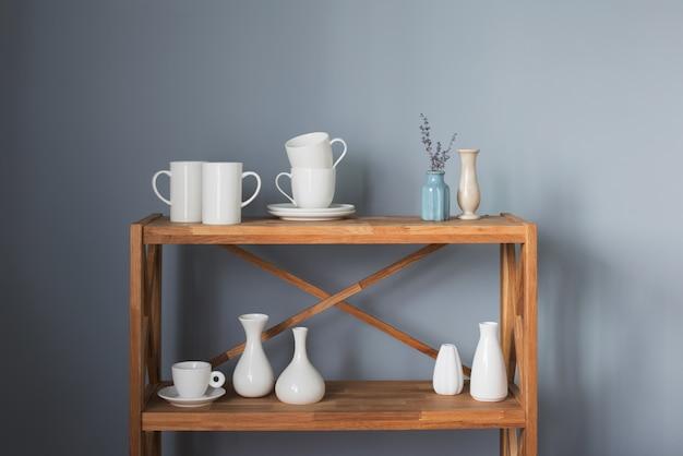 Białe kubki i wazony na drewnianej półce na szarym tle