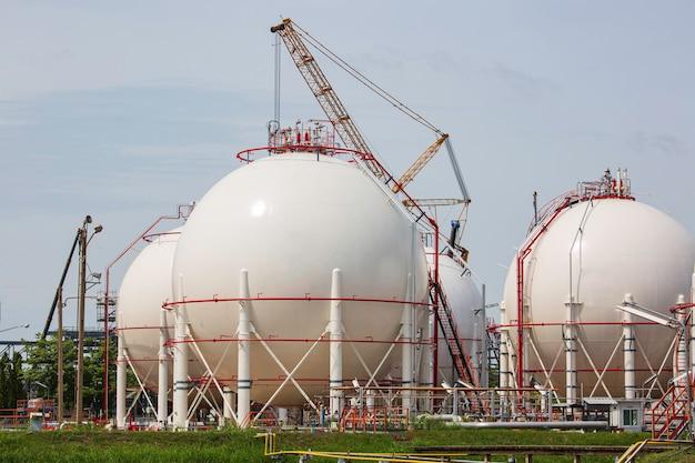 Białe kuliste zbiorniki propanu zawierające rurociąg gazowy i rusztowania