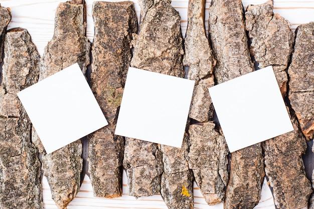 Białe kwadratowe arkusze do pisania leżą na kawałkach kory drzewa