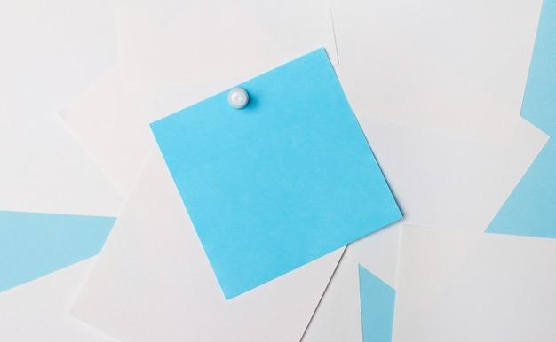 Białe kwadratowe kartki papieru na jasnoniebieskiej powierzchni