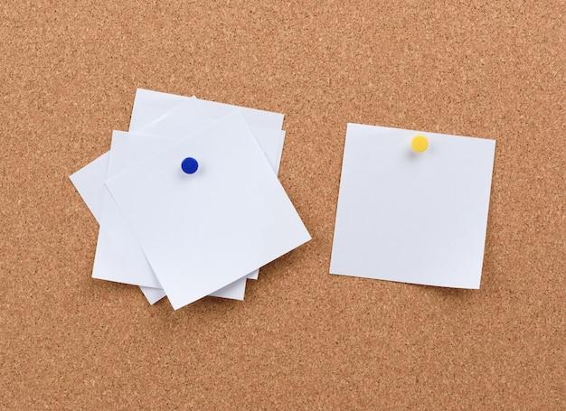Białe kwadratowe puste kawałki papieru przypięte na tablicy korkowej, kopia przestrzeń