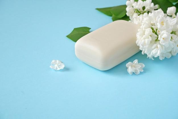 Białe kwiaty bzu i mydło na niebieskim tle koncepcja naturalnego kosmetyku