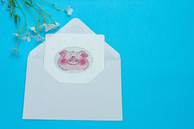 Białe kwiaty i ręcznie robiona pocztówka z krzyżem w kopercie