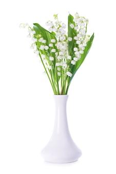 Białe kwiaty konwalii w wazonie na białym tle