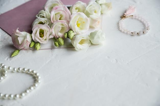 Białe kwiaty, naszyjnik z pereł, perfumy, kartka z życzeniami na białym tle. akcesoria i kwiaty. zakupy online lub randki koncepcja z miejsca na kopię.