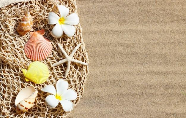 Białe kwiaty plumerii z rozgwiazdami i muszlami na siateczkowej torbie plażowej na piasku. widok z góry