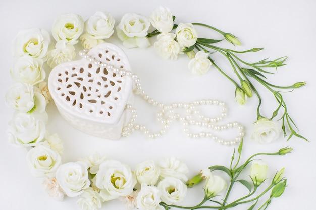 Białe kwiaty podszyte ramą i pudełkiem z biżuterią w kształcie serca