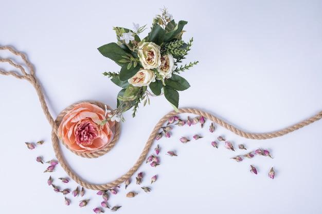 Białe kwiaty, pojedyncza róża, sznurek i płatki na białej róży.