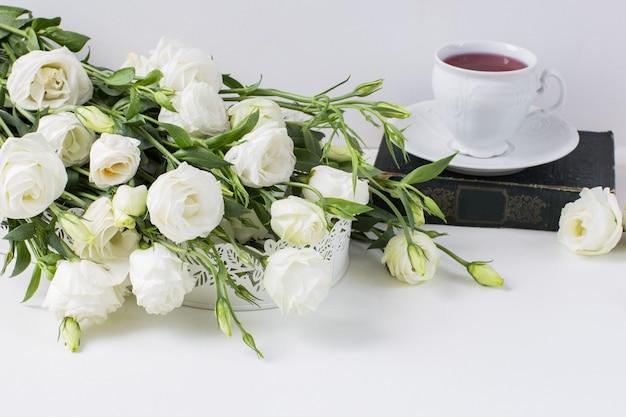 Białe kwiaty, stara książka i filiżanka herbaty
