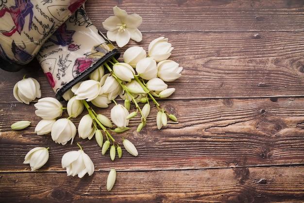 Białe kwiaty w boot wellington na teksturowane drewniane tła