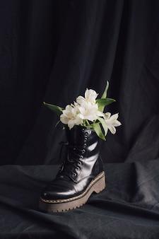 Białe kwiaty w ciemnym bucie