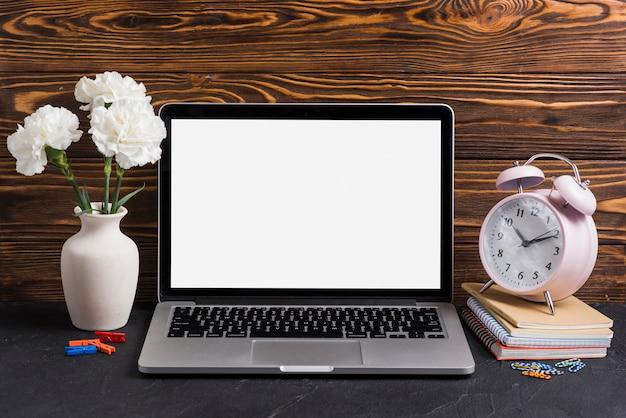 Białe kwiaty w wazonie; laptop i budzik na notatnikach przeciw drewnianemu tłu