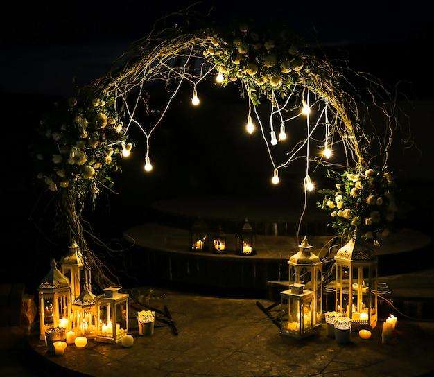 Białe kwiaty wyginają się w łuk podczas ceremonii ślubnej. dekoracja na zewnątrz. romantyczny styl rustykalny. lampy zapalają się wieczorem.