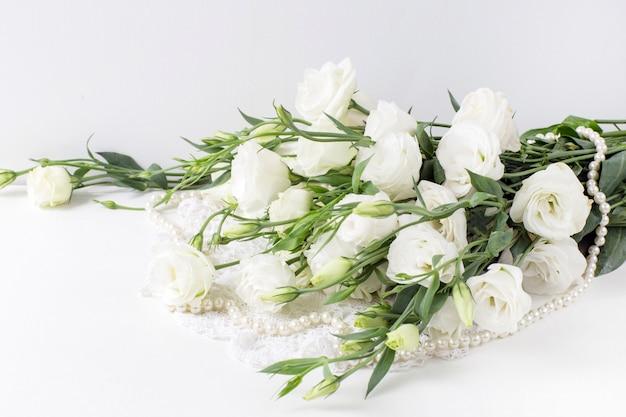 Białe kwiaty z perłowymi koralikami