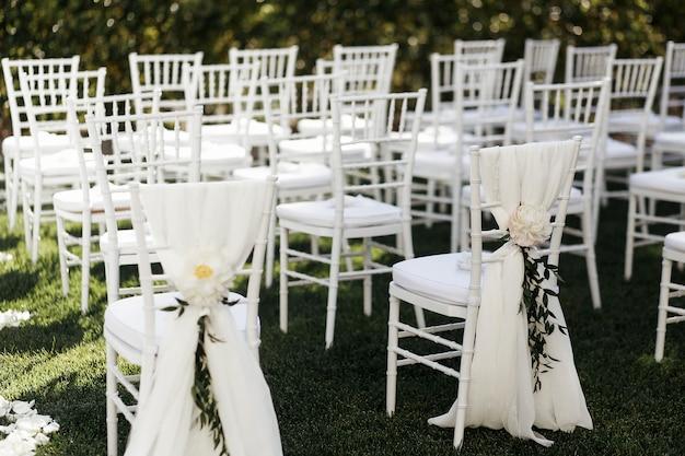 Białe kwiaty z zielonymi gałązkami dekorują krzesła