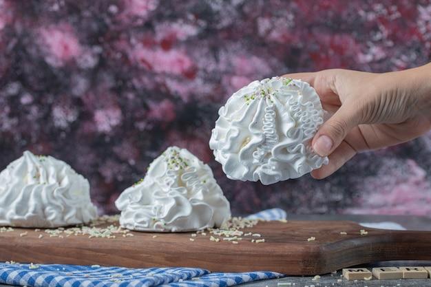 Białe kwieciste ciasteczka bezowe z proszkiem kokosowym na drewnianej desce.