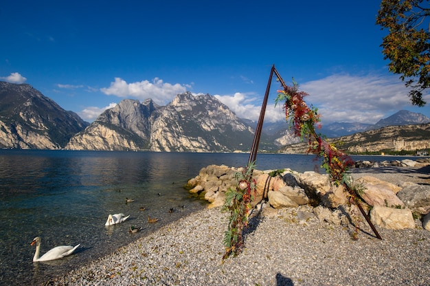 Białe łabędzie i łuk na ceremonię ślubną nad jeziorem lago di garda w alpejskim krajobrazie